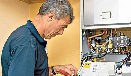 Engineer fixing a broken boiler under home emergency cover