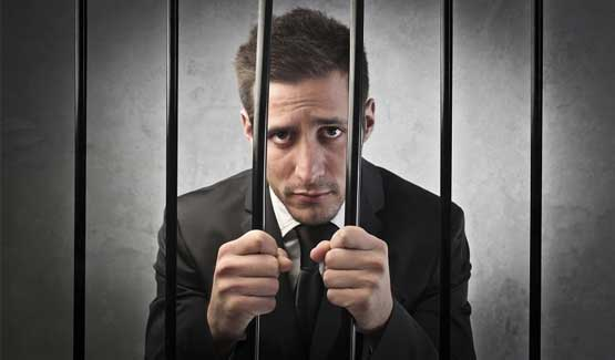 Man in a suit behind bars insinuating he is in jail.