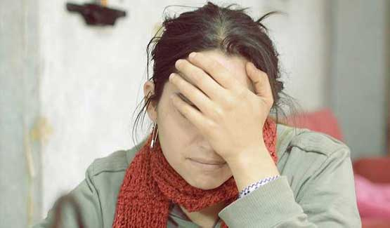 Woman with hand over face looking stressed.