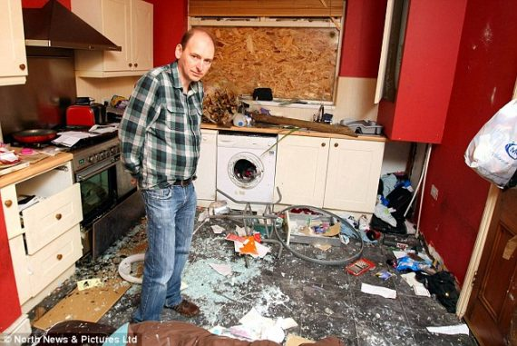 Male standing in kitchen that has been destroyed, illustrating what effects the weather can do to a property.