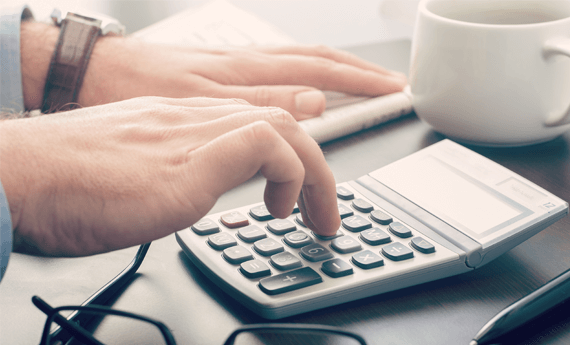 Landlord using calculator to work out how much rent to charge tenants
