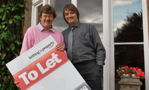 Female landlord with male tenant holding a lettingaproperty.com To-Let sign standing outside the property.