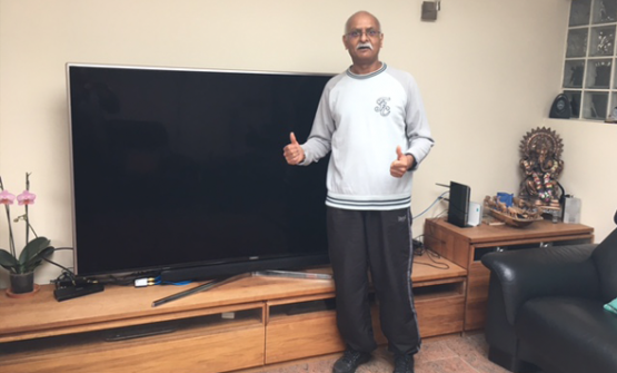 Male landlord with two thumbs up, standing in front of a new TV purchased with savings made using lettingaproperty.com.