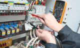 Fixed Wire Testing being carried out by competent electrician testing fuse board.