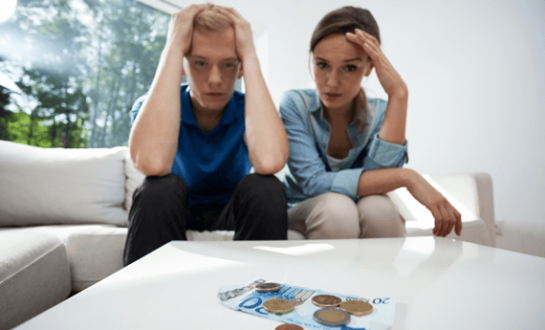 Tenants in rent arrears sat on sofa looking at money on table