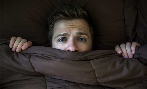 Man hiding under the covers having heard property news