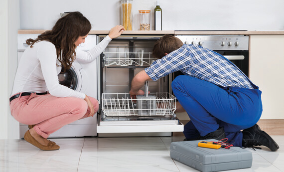 Plumber fixing dishwasher in front of lady tenant under landlord repair responsibilities