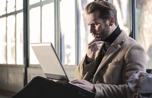 Confused man staring at a laptop