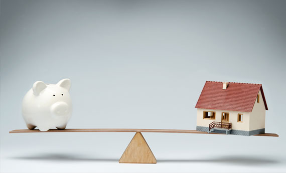 Money bank pig and a house on a seesaw