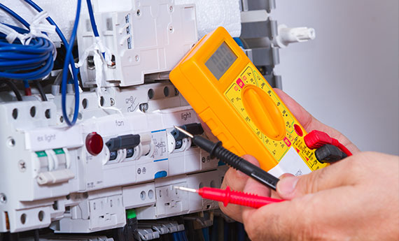 Electrician with multi meter doing an electrical safety check