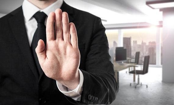 Man in black suit saying no with raised hand